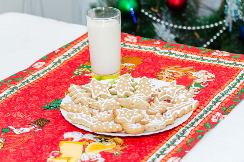 High angle view of gingerbread cookies by drink on table during christmas