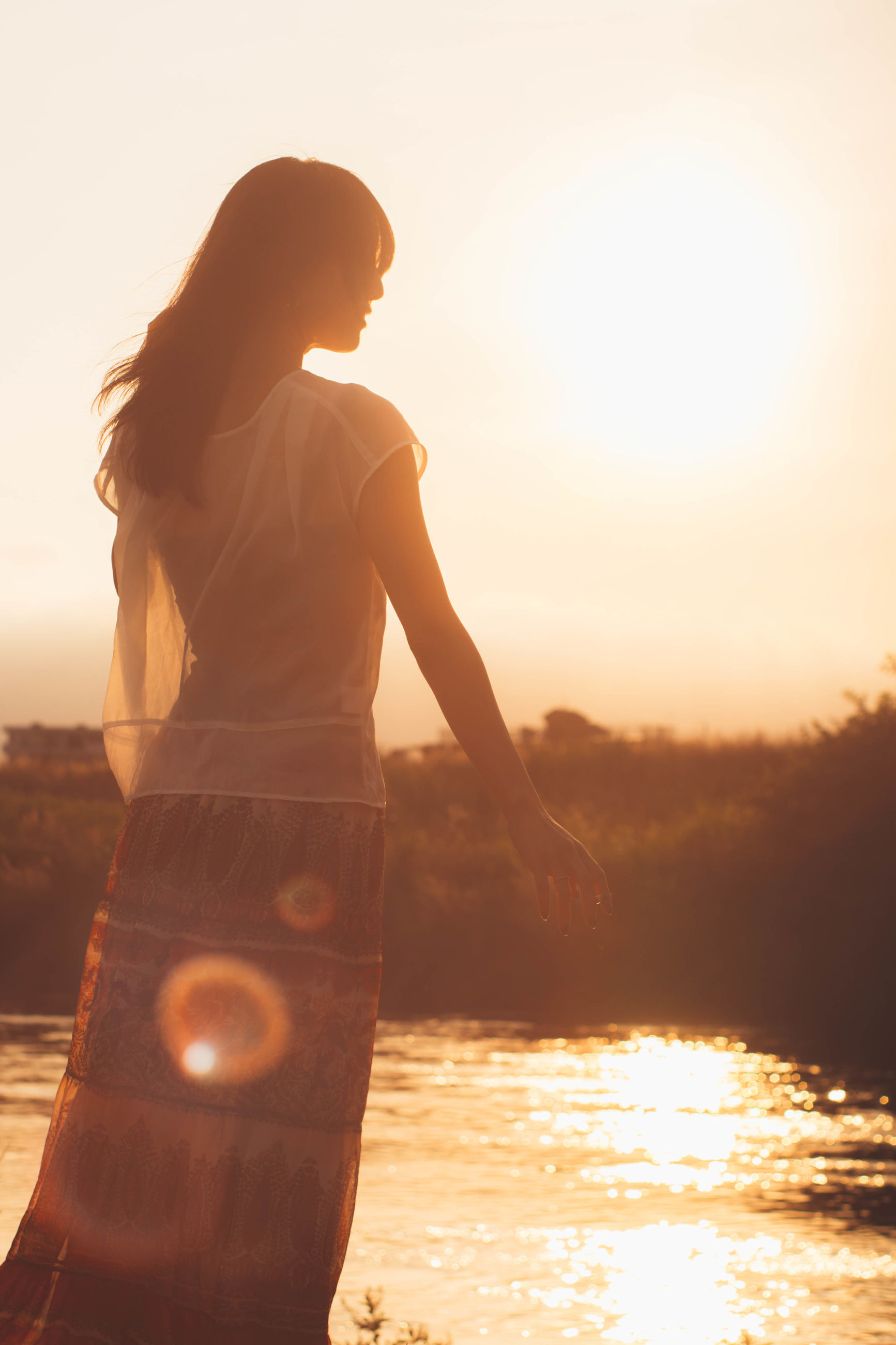 sunset, real people, one person, water, sun, leisure activity, nature, standing, lifestyles, outdoors, beauty in nature, sky, rear view, sunlight, women, childhood, scenics, sea, full length, clear sky, tree, day, young adult, people