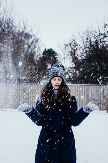 Photo in defocus. young attractive girl throwing snow with her arms. closeup shot.