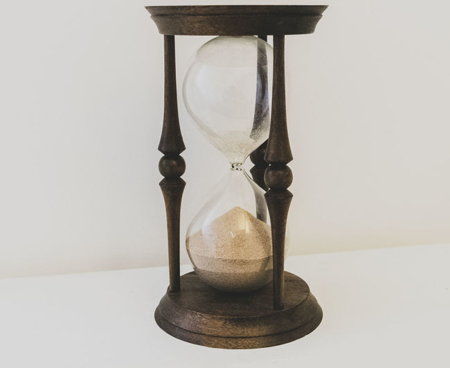 Close-up of clock falling on glass table