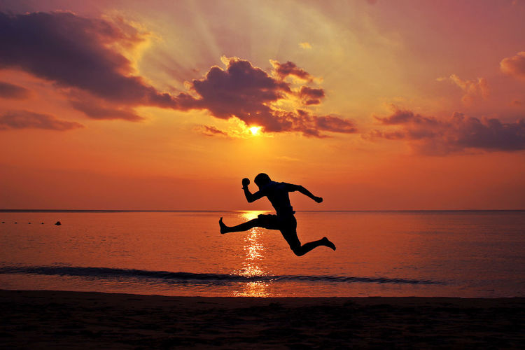 Side View Of Man With Arms Outstretched Jumping At Beach At Sunset