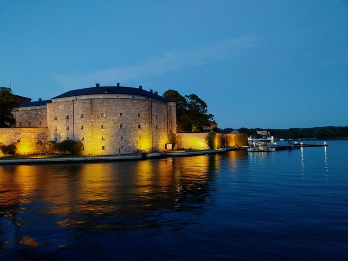 Vaxholm fortress by lake in city at dusk