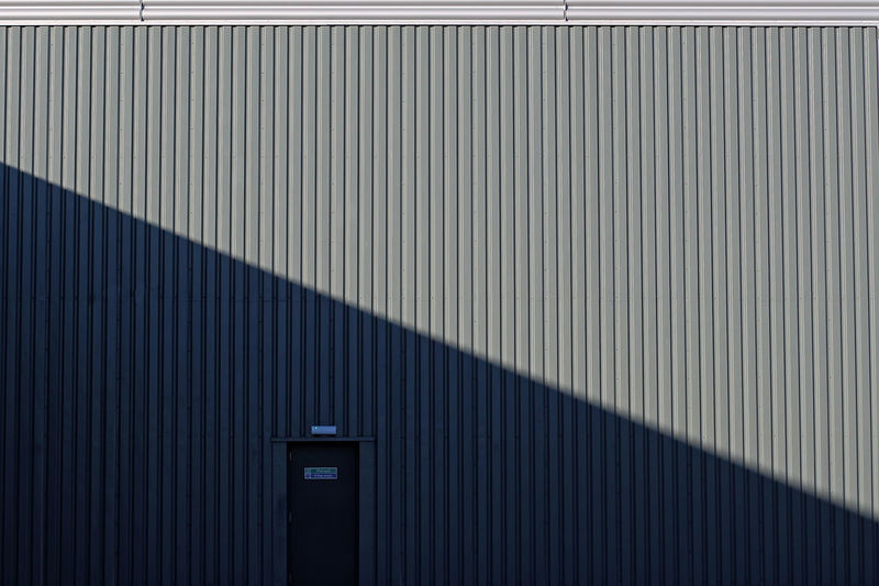 The door. Shadows & Lights Architecture Building Exterior Built Structure City Closed Corrugated Corrugated Iron Day Entrance Fire Exit  Iron Metal No People Pattern Security Shadow Shapes And Forms Sign Silver Colored Sunlight Textured  Wall - Building Feature
