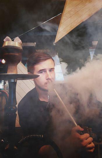 Portrait of young man smoking hookah