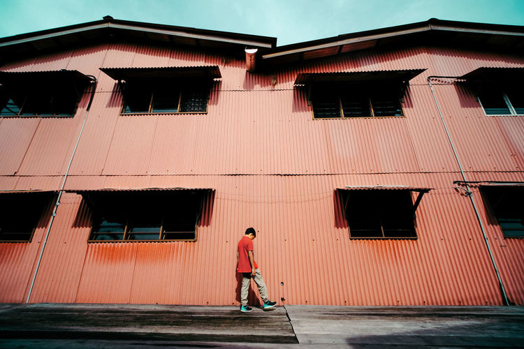 Rear View Of Man Standing Against Building