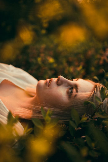 Portrait of woman lying down on leaves