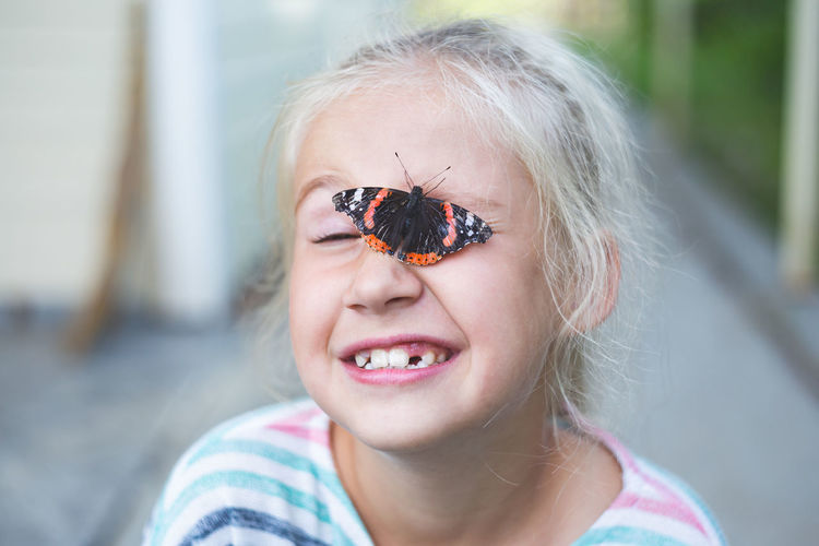 A beautiful black butterfly with orange spots sits on face of a cheerful blonde  girl 7-8 years.