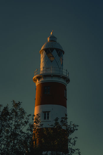 Low angle view of lighthouse by building against sky at night