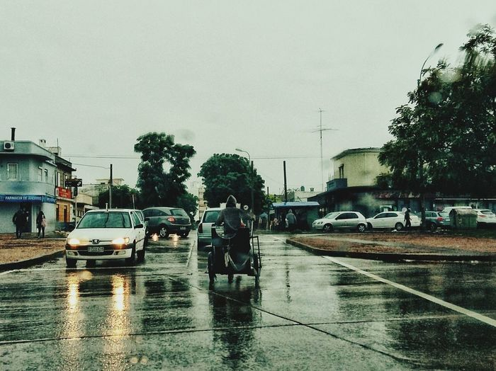 Cars on wet street against sky during monsoon