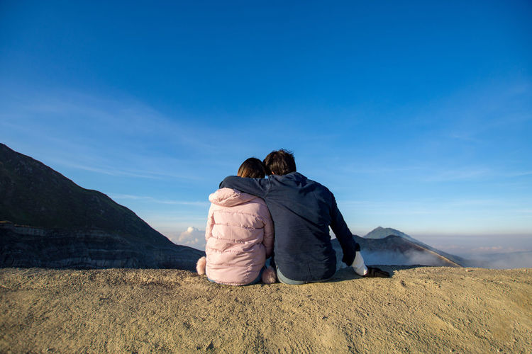 INDONESIA Adult Arm Around Blue Bonding Couple - Relationship Kawah Ijen Land Landscape Leisure Activity Lifestyles Love Men Mountain Mountain Range Nature Outdoors People Positive Emotion Real People Rear View Sky Togetherness Tourism Travel Destinations Two People Women