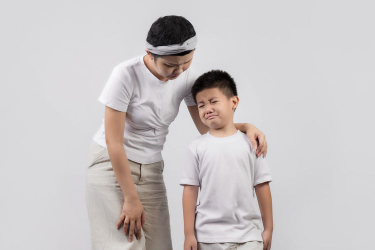 Father and son standing against white background
