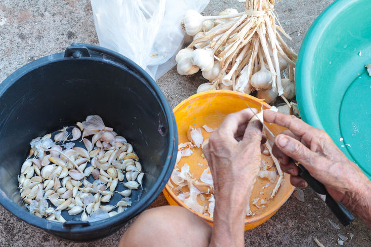 Midsection of man peeling garlic by containers