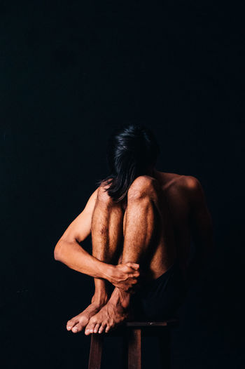 Full length of depressed man sitting on stool against black background