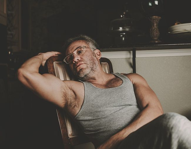 Thoughtful muscular mature man sitting on chair at home