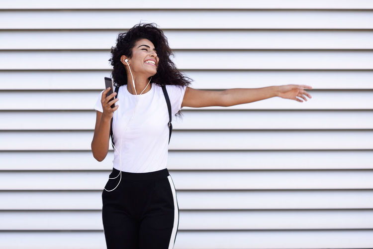 Funny African woman listening to music and dancing with earphones and smartphone outdoors. Arab girl in sport clothes with curly hairstyle in urban background. Earphones Adult Architecture Arms Raised Beautiful Woman Casual Clothing Front View Hair Hairstyle Human Arm Leisure Activity Lifestyles Looking Looking Away One Person Portrait Smart Phone Smiling Standing Three Quarter Length Wall - Building Feature Young Adult Young Women