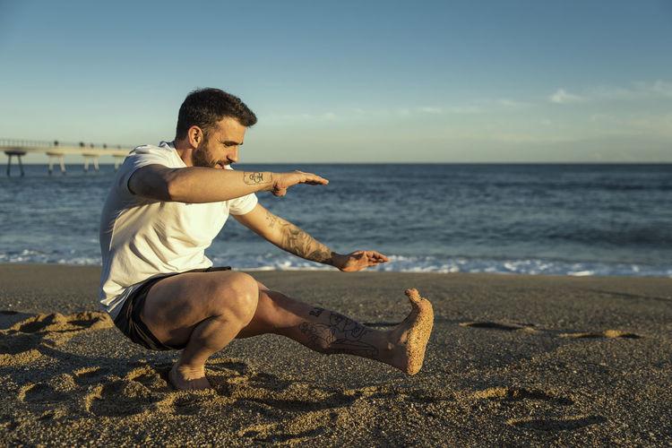 Full Length Of Man Doing Stunt At Beach Against Sky