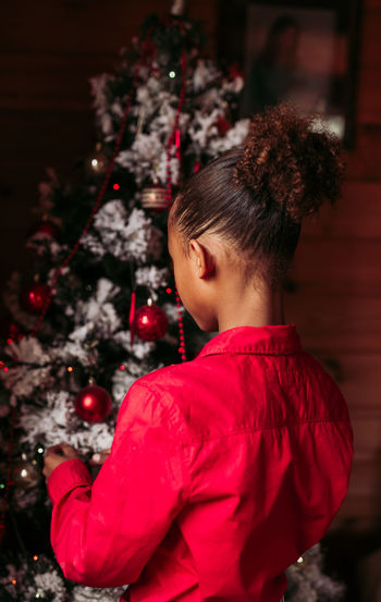 Girl with red christmas tree
