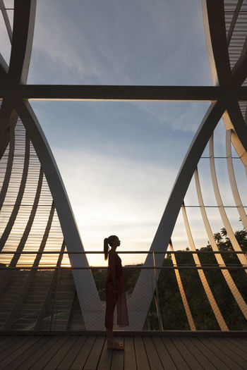 Side view of woman standing on footbridge against sky at sunset