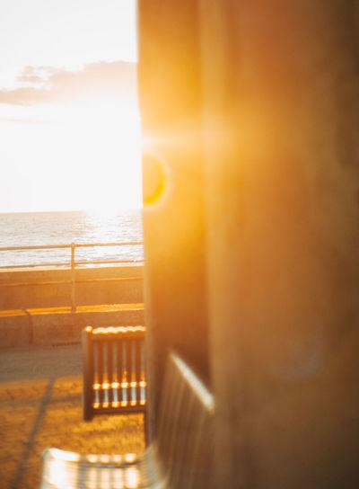 Sea seen through window during sunset