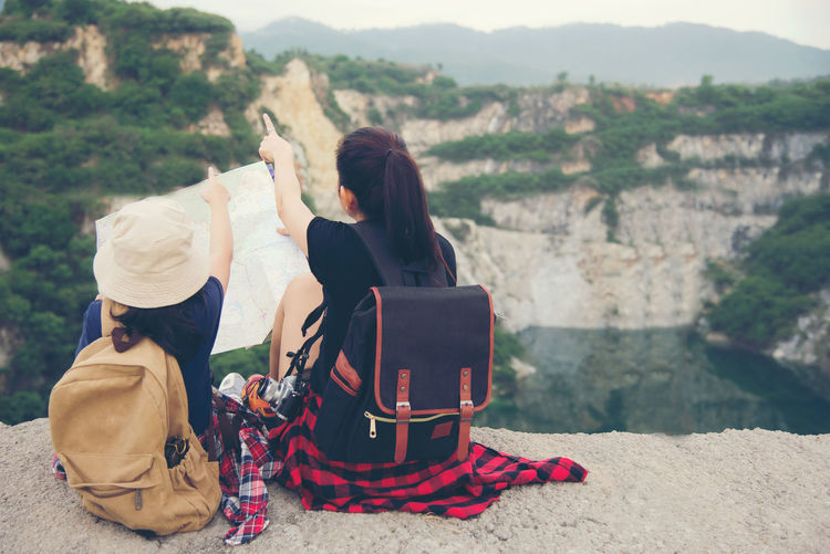 People sitting on mountain looking at view