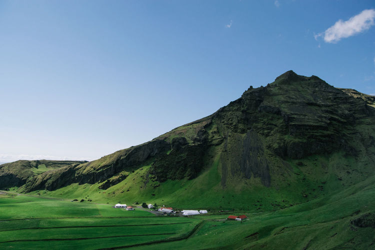 Scenic view of houses in green, lush, rolling mountains