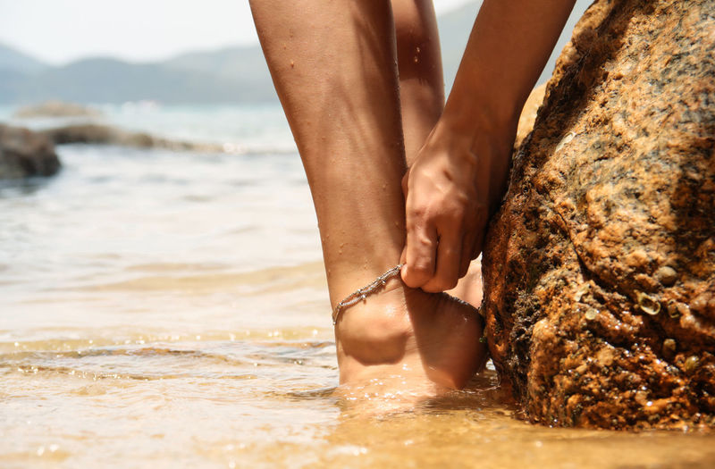 Low section of woman adjusting anklet in sea