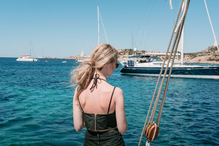 Blue Casual Clothing Clear Sky Day Long Hair Nature Nautical Vessel Outdoors Person Sailboat Sea Ship Standing Summer Sunlight Sunny Tranquility Turquoise Colored Vacations Water Waterfront Weekend Activities Young Adult