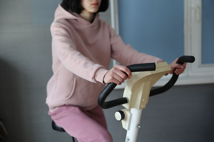 Midsection of woman holding bicycle standing against wall