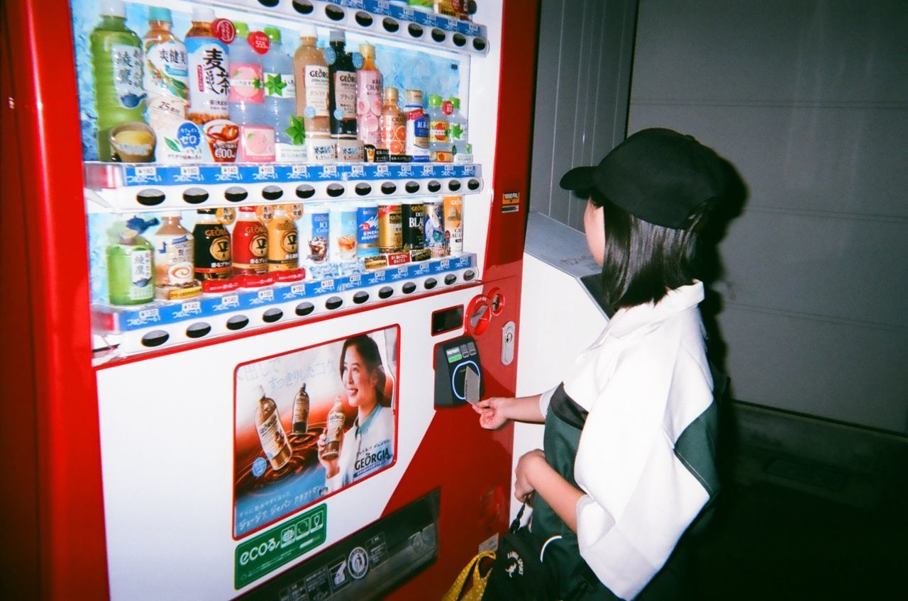 indoors, one person, machinery, lifestyles, vending machine, technology, real people, women, occupation, food and drink, adult, business, appliance, men, working, standing, refrigerator, waist up, innocence