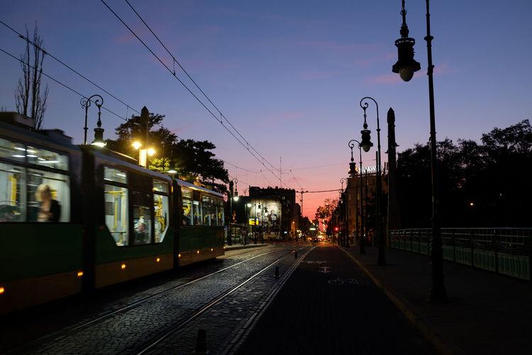 Train on railroad tracks against sky at sunset
