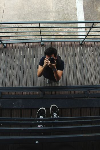 High Angle View Of Man Photographing While Standing On Footbridge