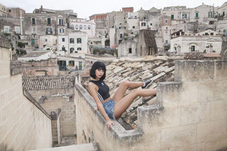 Woman sitting against buildings in city