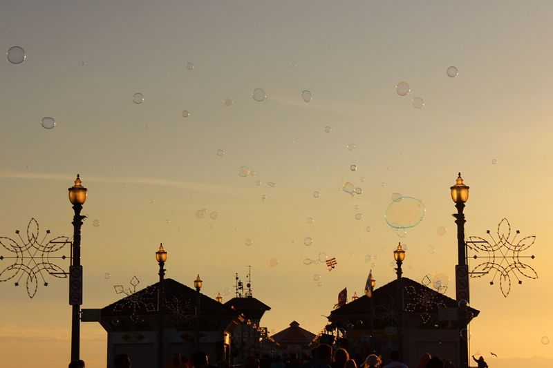 Low angle view of bubbles over huntington beach pier against sky during sunset