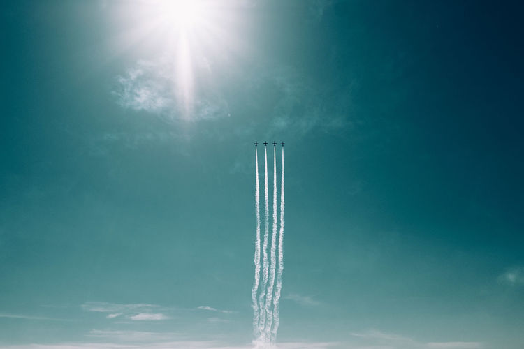 Low angle view of airshow in blue sky