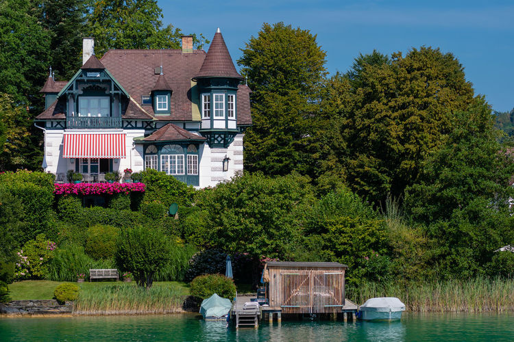 WORTHERSEE, AUSTRIA - AUGUST 08, 2018: Great scenery from the boat to the shore line of the lake, beautiful buildings, mountains, forests, highways. Tourists who enjoy a variety of water recreation types. Nature Day Outdoors Austria Carinthia Carinthian Lakes Tourist Tourists Lake Wörthersee Recreation  Leisure Landscape Water Sea Boats Motorboat Speedboats Summer People Holidays Fun Travel Beach Resort Lifestyle Sunny Rest Joy Waves Europe Alps Alpine Alpine Lake Tree Architecture Plant Built Structure Building Building Exterior House No People Waterfront Residential District Transportation Growth Beauty In Nature Luxury