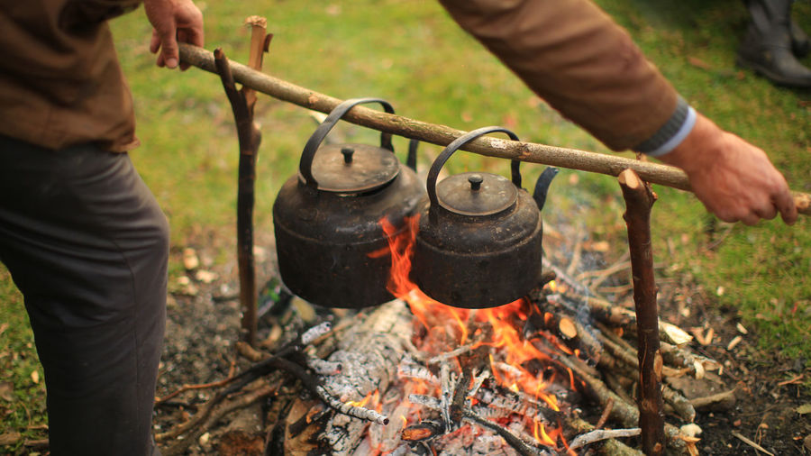 Midsection of man preparing food over bonfire