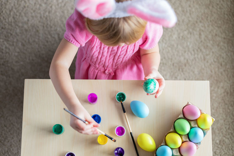 Little girl in easter bunny ears painting colored eggs. easter family holiday celebration at home.