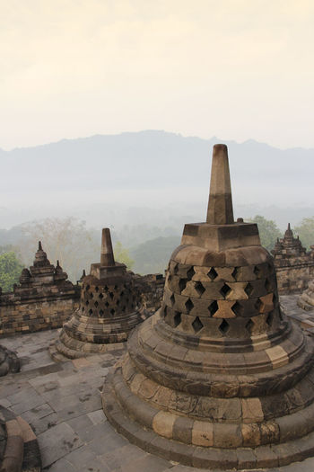 Borobudur Temple with the mysteries forest surrounding during sunrise, Yogyakarta, Indonesia Yogyakarta Ancient Ancient Civilization Architecture Belief Borobudur Buddhist Temple Building Exterior Built Structure Fog Forest History Nature No People Place Of Worship Religion Sky Spirituality Sunrise The Past Tourism Travel Travel Destinations