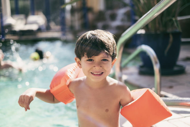Portrait of shirtless smiling boy with water wings in swimming pool