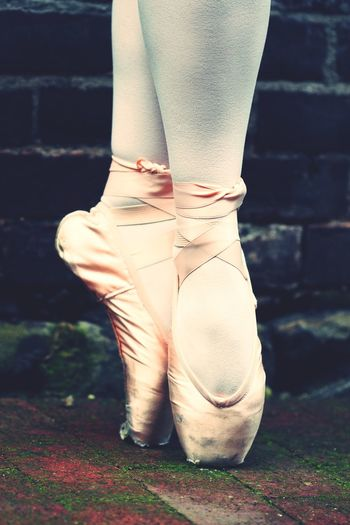 Low section of ballet dancer against wall