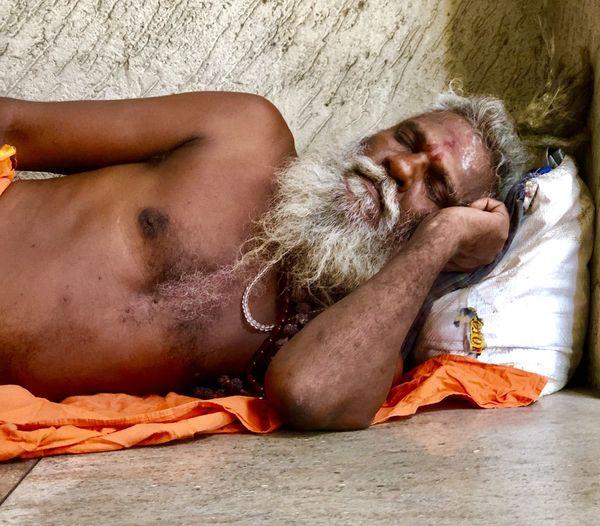 Sadhu sleeping on floor against wall