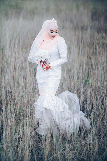 Beautiful malay Bride Field Plant Land Grass One Person Women Nature Young Adult Three Quarter Length White Color Day Adult Front View Standing Leisure Activity Fashion Females Full Length Outdoors Mouth Open