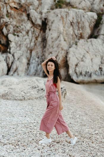 Full length portrait of woman walking at beach