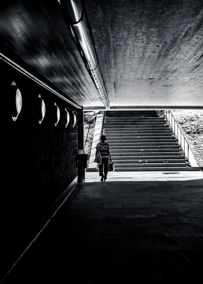 Rear view of man walking in subway tunnel
