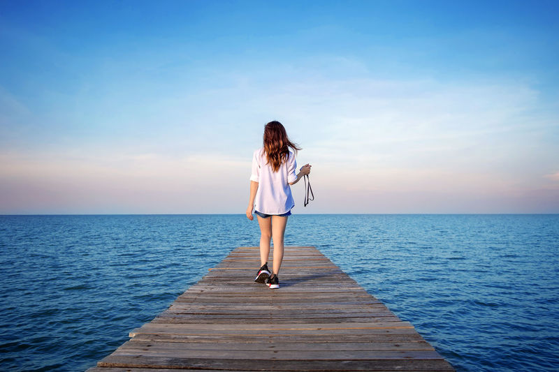 Woman walking on wooden bridge extended into the sea. Adult Beauty In Nature Clear Sky Day Full Length Horizon Over Water Leisure Activity Lifestyles Nature One Person Outdoors People Real People Scenics Sea Sky Standing Tranquil Scene Tranquility Water Young Adult Young Women