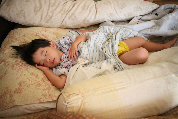 High Angle View Of Child Sleeping On Bed