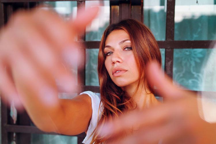 Portrait of woman against window
