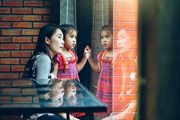 Mother and daughter looking out through the windows Adult Brick Brick Wall Consumerism Females Glass - Material Lifestyles Looking Positive Emotion Real People Retail  Retail Display Selective Focus Shopping Store Store Window Togetherness Transparent Two People Window Window Shopping Women