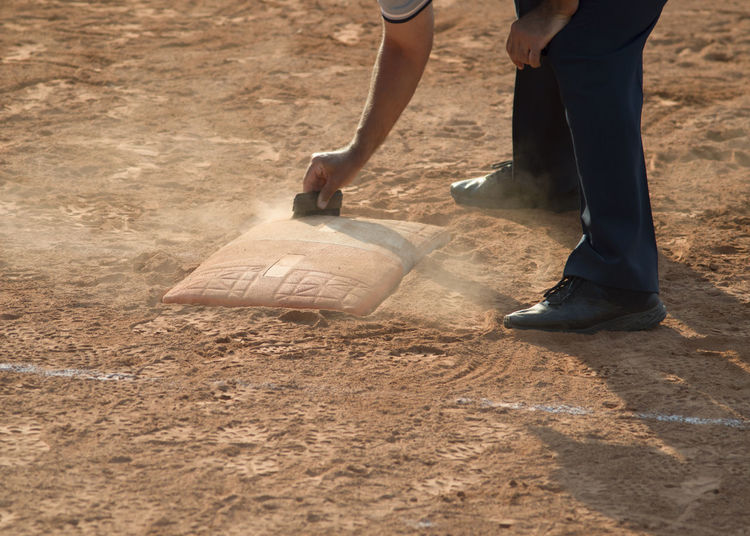 Referee cleans home plate in a baseball (softball) dusty field, with copyspace Adult Body Part Day Dust Field Holding Human Body Part Human Foot Human Leg Land Lifestyles Low Section Men Nature Occupation Outdoors People Real People Standing Sunlight Two People
