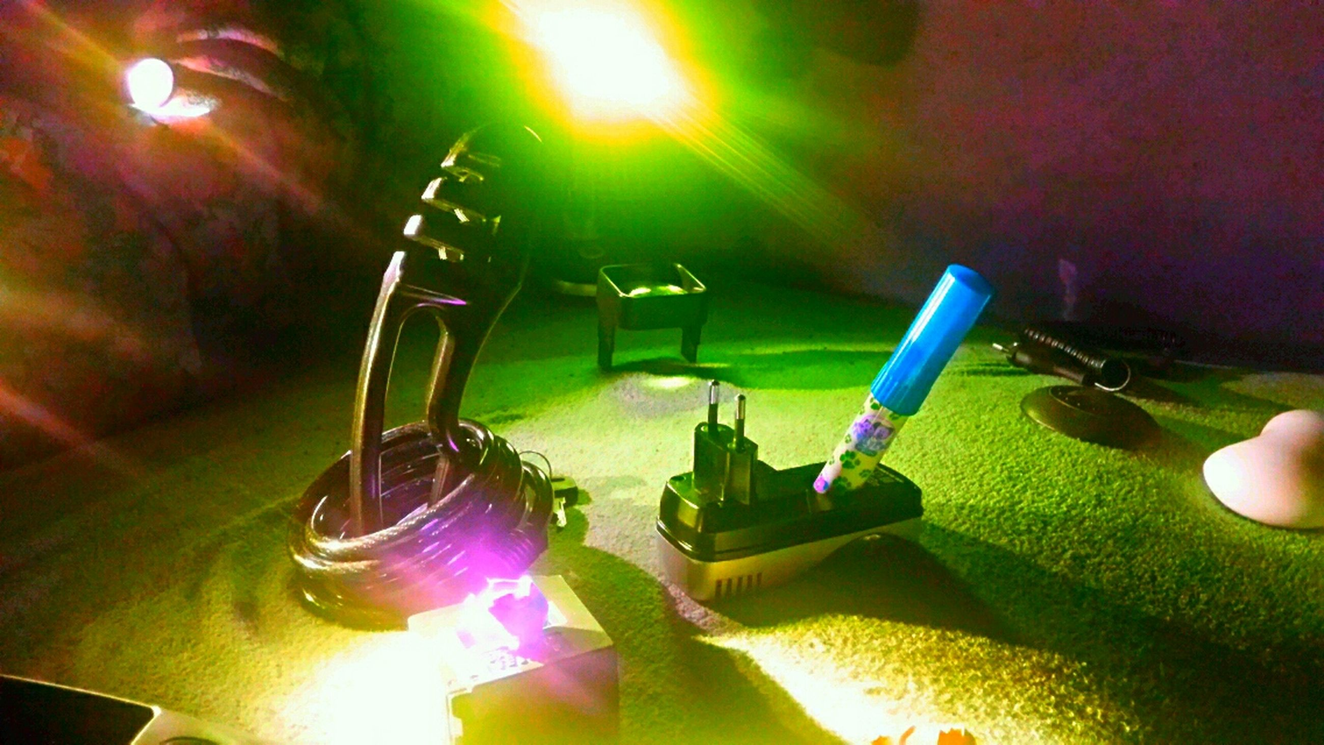 indoors, illuminated, close-up, lighting equipment, light - natural phenomenon, lens flare, focus on foreground, table, sunlight, glowing, no people, high angle view, green color, selective focus, decoration, reflection, light beam, night, part of, shiny